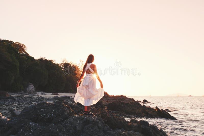 放松靠近海洋偏僻的感觉的亚裔妇女在日落时间 免版税库存照片