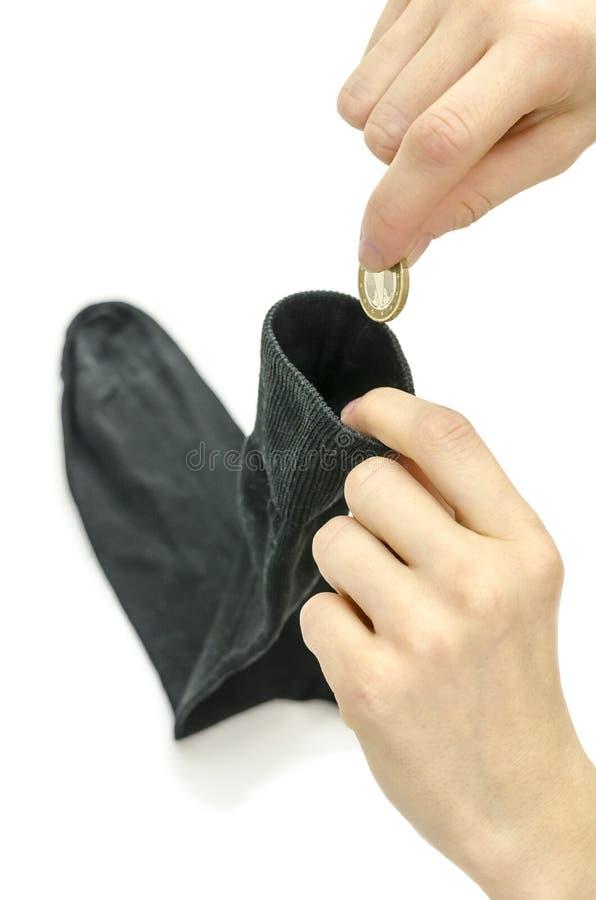 放欧洲硬币的女性手入袜子 免版税图库摄影