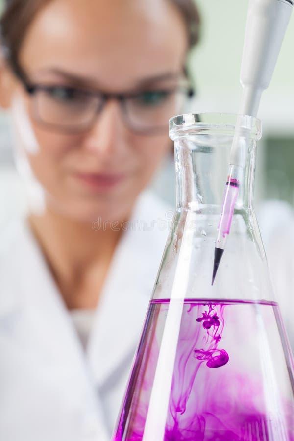 放液体的化学家入烧瓶使用吸移管 免版税库存照片