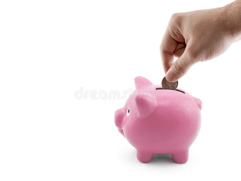 放硬币入存钱罐 免版税库存图片