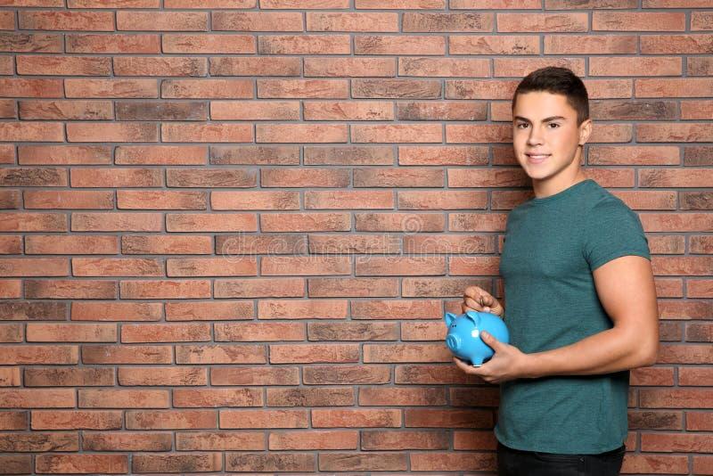 放硬币的十几岁的男孩入存钱罐在砖墙附近 库存图片