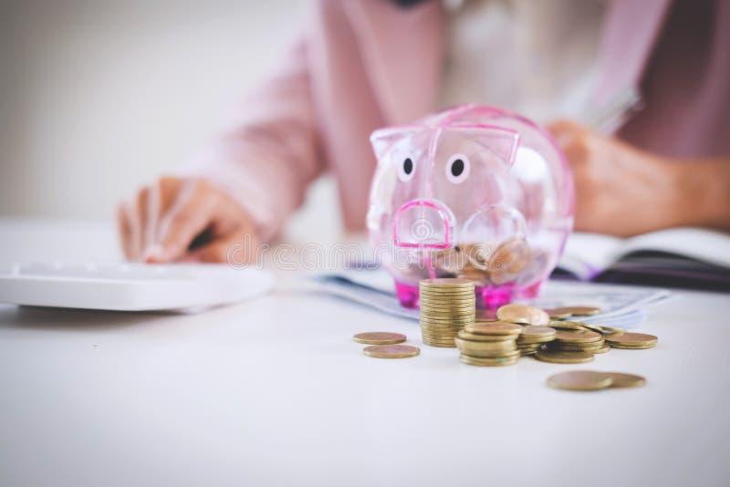 放硬币的女商人入存钱罐,写给报告 免版税图库摄影