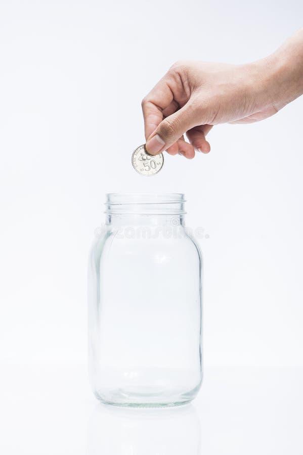 放硬币的女性手的图象入空的玻璃瓶 图库摄影