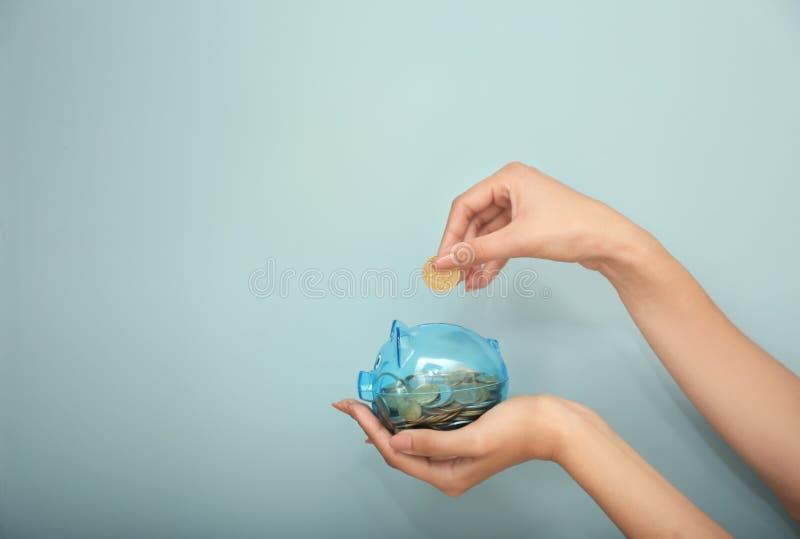 放硬币的妇女入存钱罐在开关墙壁附近 电挽救概念 免版税库存照片