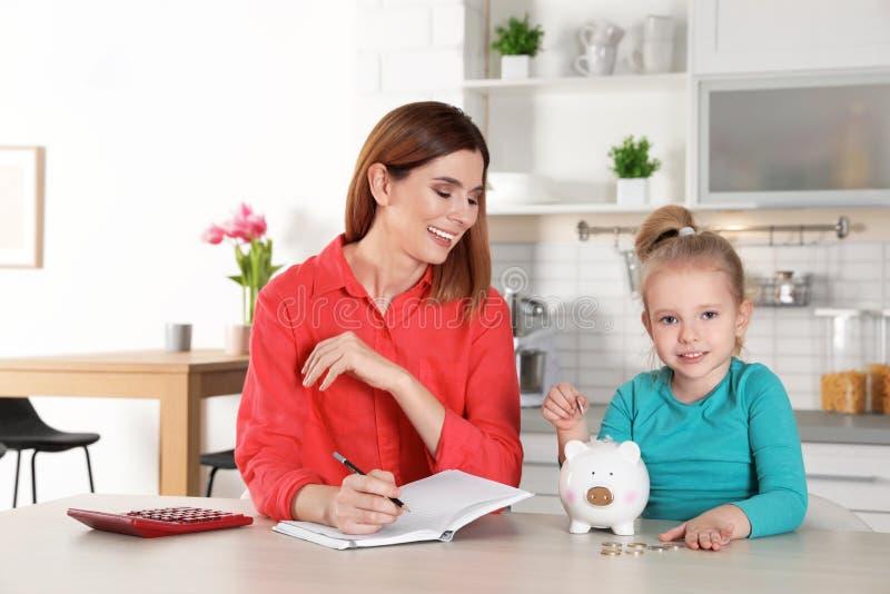 放硬币的母亲和女儿入存钱罐在桌上户内 免版税库存图片