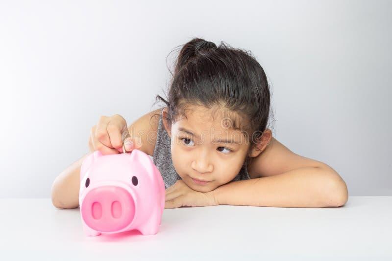放硬币的逗人喜爱的亚裔女孩入存钱罐 图库摄影