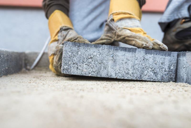 放置一个铺路板的建筑承包商 免版税图库摄影