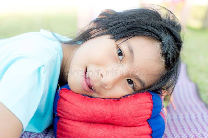 放置与枕头的愉快的亚裔女孩室外 库存图片