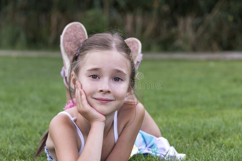 放置和摆在草的女孩 免版税库存照片