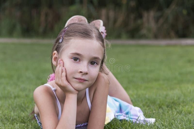 放置和摆在草的女孩 库存照片