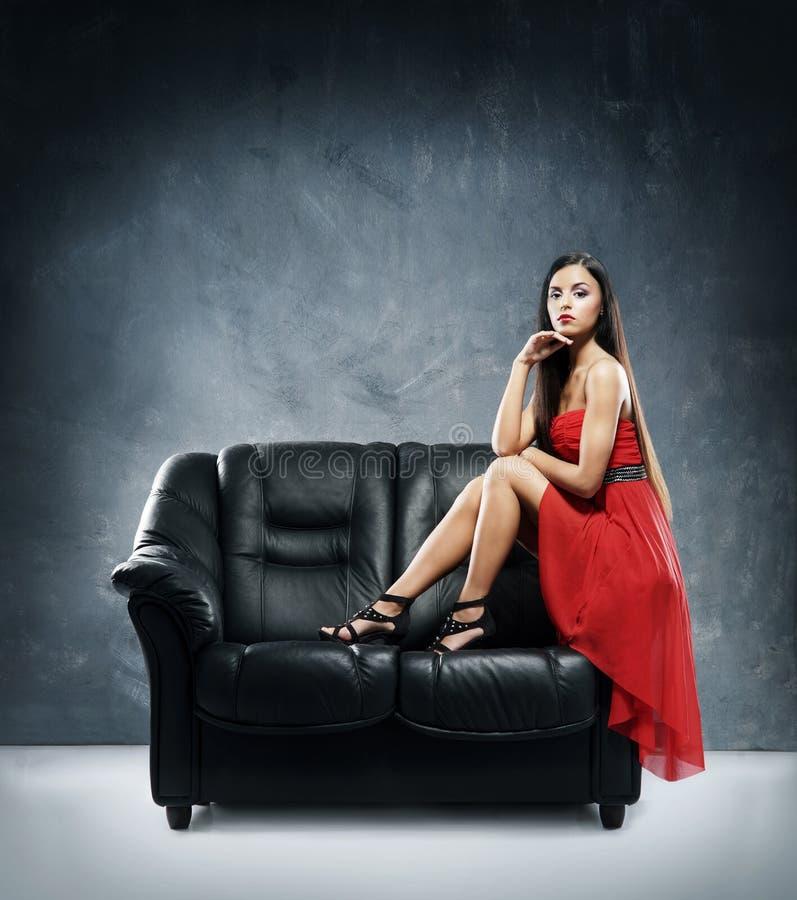 放置在一个黑沙发的一件红色礼服的一个少妇 免版税库存图片