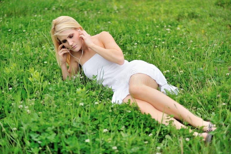 放置在三叶草的领域的美好的年轻女性白肤金发的模型 库存照片