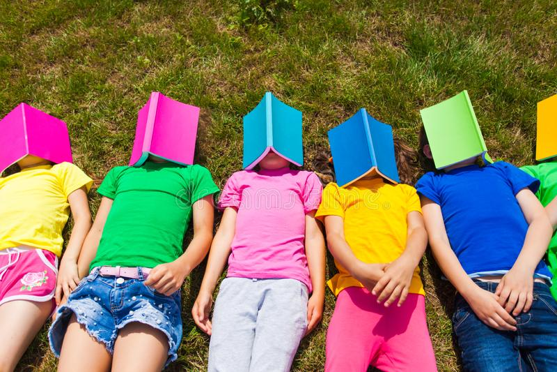 放置在与书的地面的四个孩子在他们的面孔 免版税库存照片
