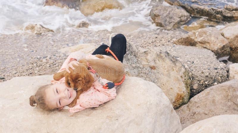 放置在与她的甜小狗的岩石的女孩 免版税库存图片