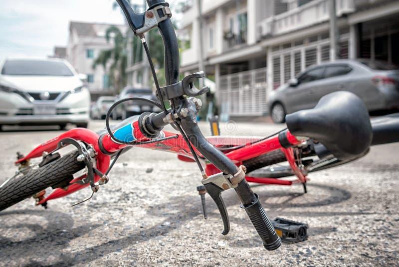 放置在交通事故的柏油碎石地面的儿童的自行车 免版税库存照片