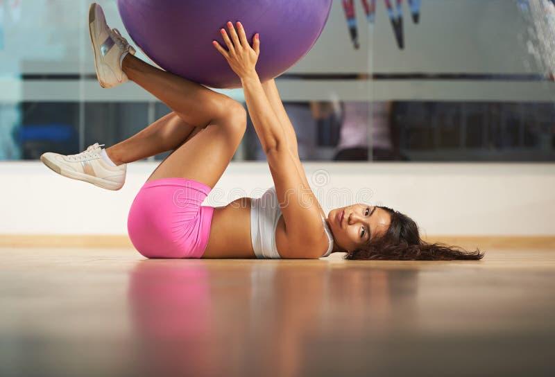 放置在健身俱乐部flooor的少妇 库存图片