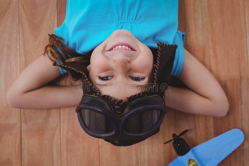 放置在地板佩带的飞行员玻璃和帽子的微笑的女孩 免版税库存图片
