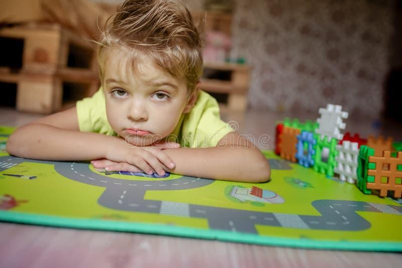 放置在地板的可爱的gingerish小男孩,使用与大厦立方体 免版税图库摄影