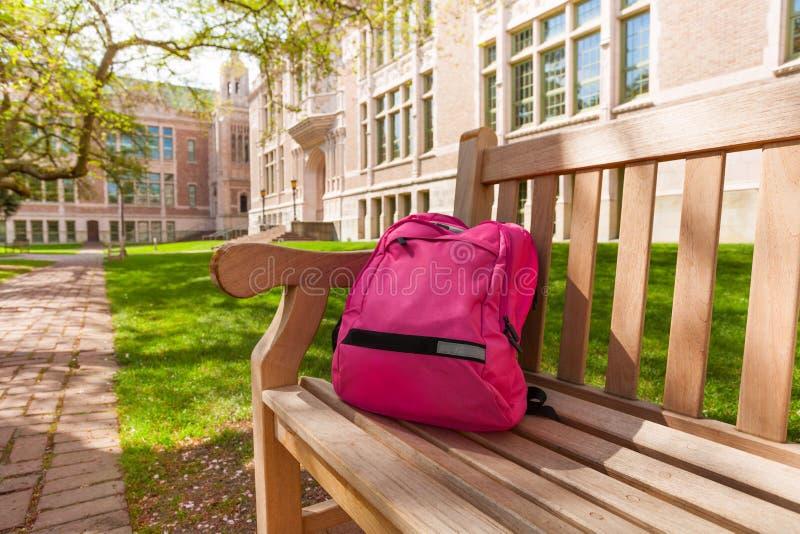 放置在大学长凳的背包 免版税库存照片