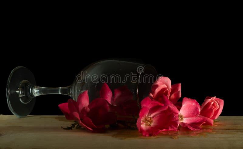 放置在它的与桃红色玫瑰花束的边的酒杯  库存图片