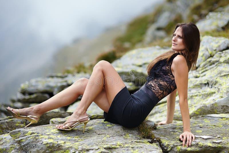 放置在山岩石的端庄的妇女 免版税库存照片