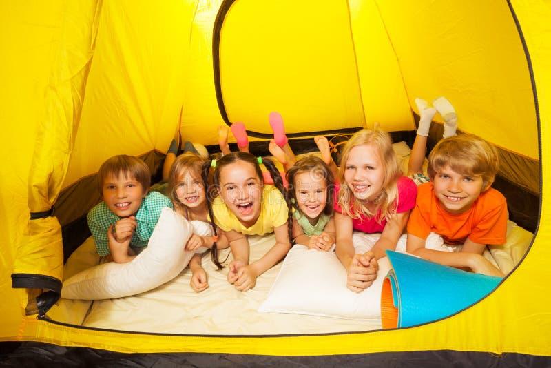 放置在帐篷的小组孩子 免版税库存图片