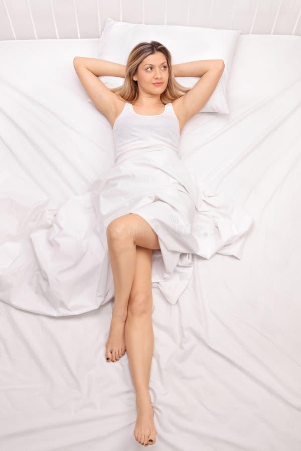 放置在床上的沉思少妇 免版税库存图片