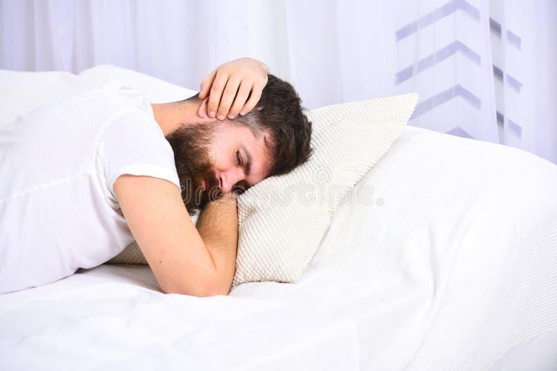 放置在床覆盖物耳朵的衬衣的人用手,在背景的白色帷幕 叫醒电话概念 有胡子的强壮男子 图库摄影