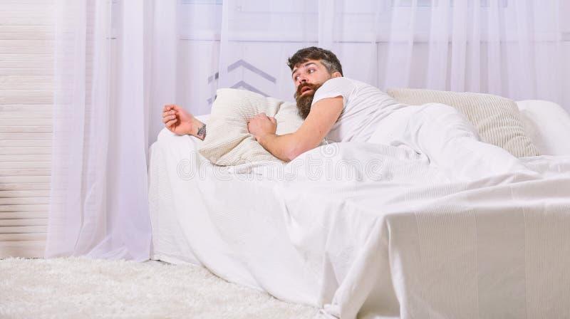 放置在床醒,在背景的白色帷幕的衬衣的人 醒并且睡过头概念 有胡子的强壮男子和 免版税库存图片