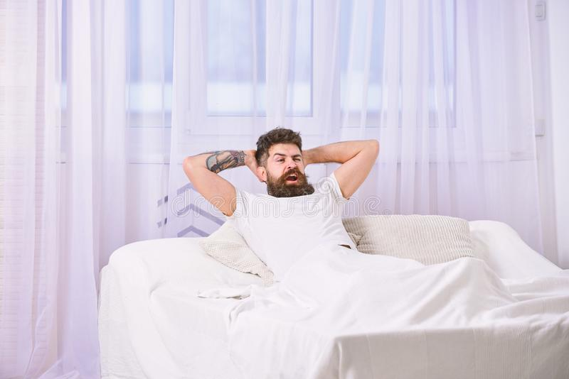 放置在床,在背景的白色帷幕的衬衣的人 充分满意的面孔的人的能量在早晨 充分  库存照片