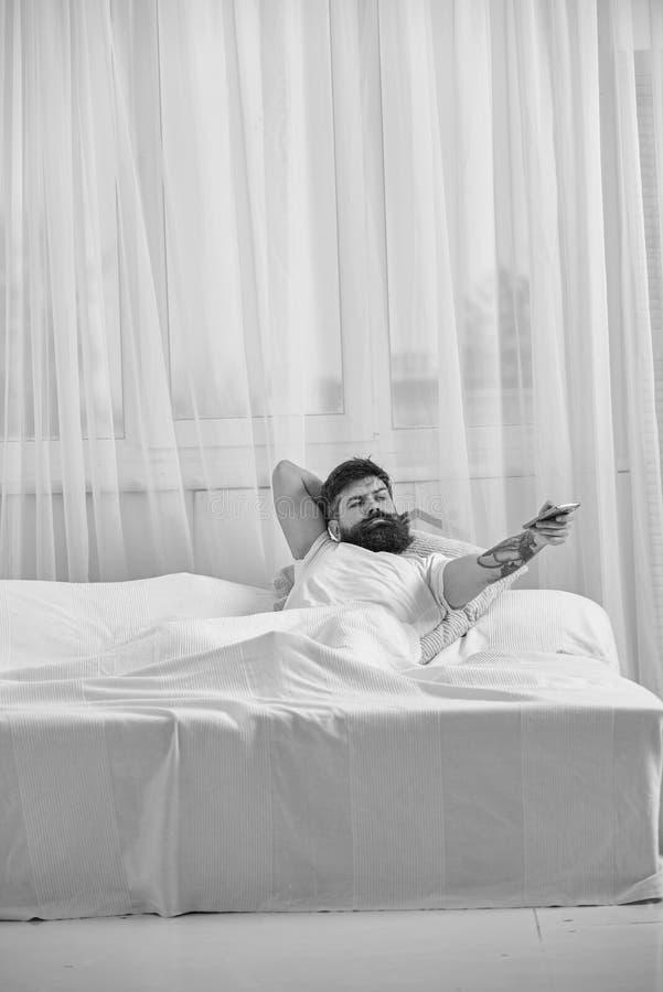 放置在床,观看的电视,在背景的白色帷幕的衬衣的人 有胡子的强壮男子拿着控制器手中 远程 库存图片