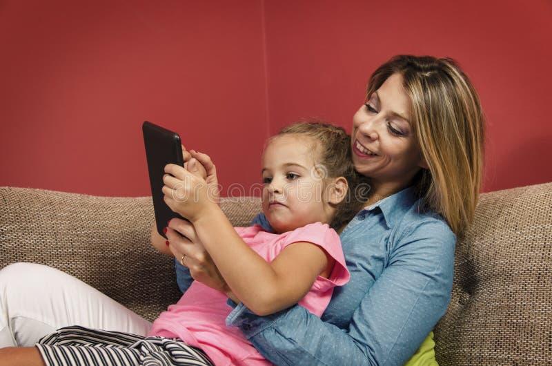 放置在有她的使用片剂的母亲的长沙发的小女孩 库存照片