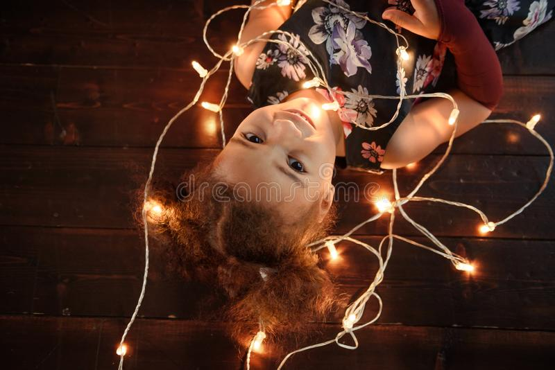 放置在有明亮的圣诞节诗歌选的弗洛尔的逗人喜爱的女孩在她的头发 免版税图库摄影