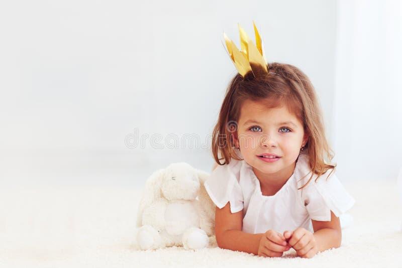 放置在有玩具兔宝宝的地毯的逗人喜爱的矮小的女婴画象  库存图片