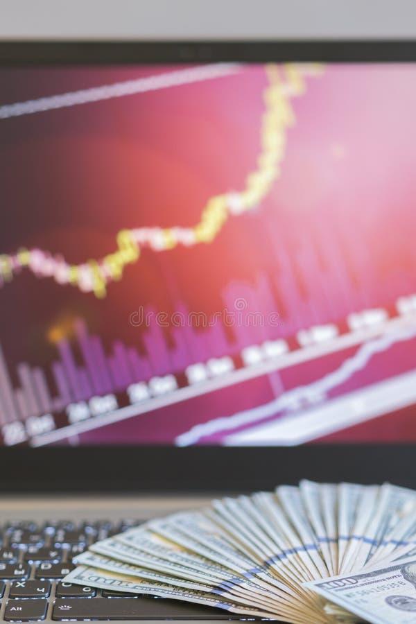 放置在有bitcoin图的一台膝上型计算机的美金在被弄脏的背景 r 图库摄影