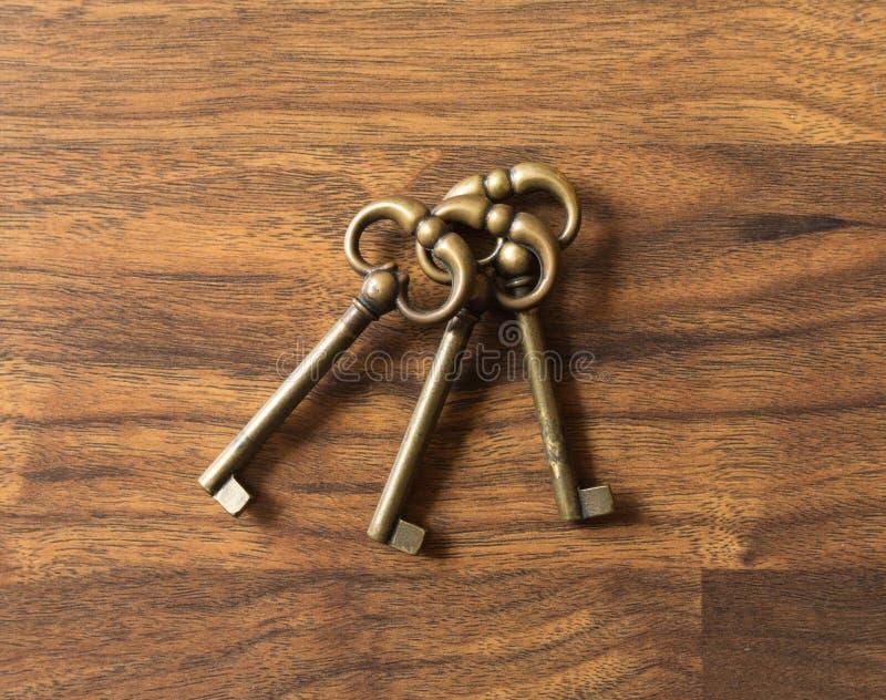 放置在木表面的三把相同古铜色钥匙 免版税库存图片