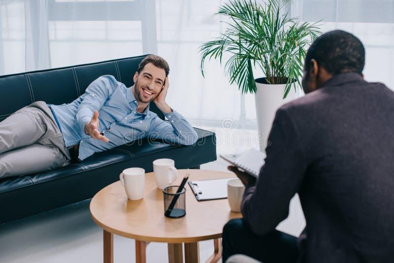 放置在沙发和顾问文字的微笑的患者 库存图片