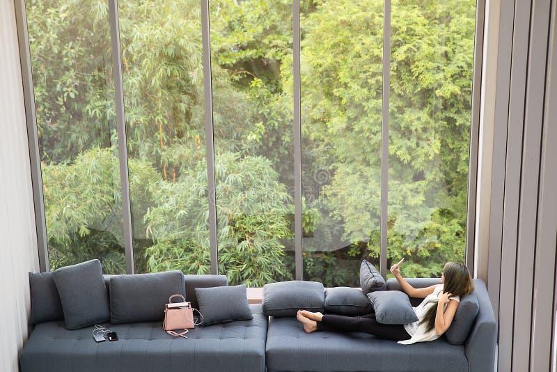放置在沙发在大玻璃wondows附近,松弛alon的亚裔妇女 库存照片