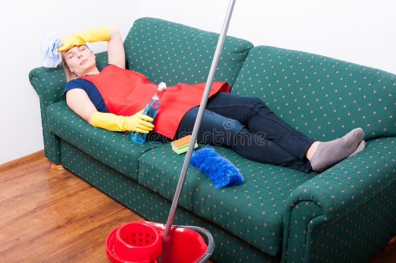 放置在沙发的主妇,当清洗屋子时 库存照片