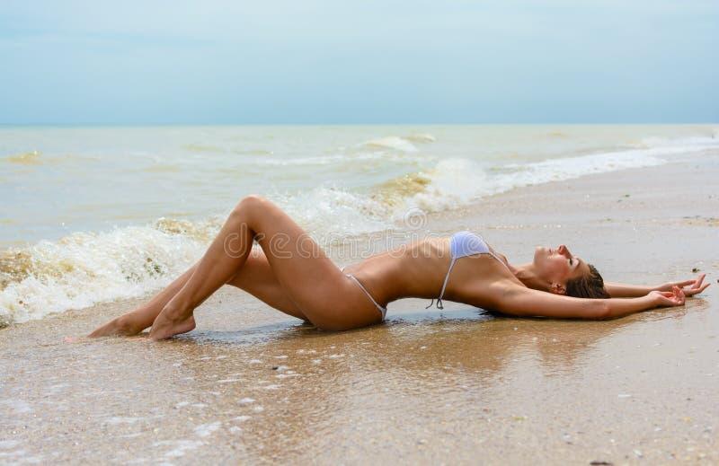 放置在沿海的美丽的少妇 免版税库存照片