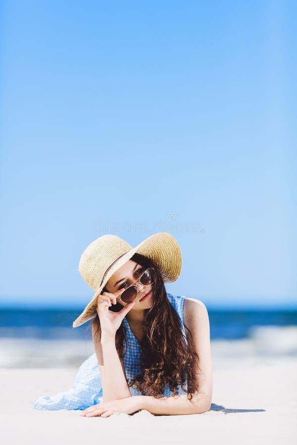 放置在海滩的年轻俏丽的妇女 图库摄影