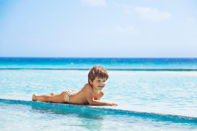 放置在游泳池的房客的愉快的男孩 库存照片