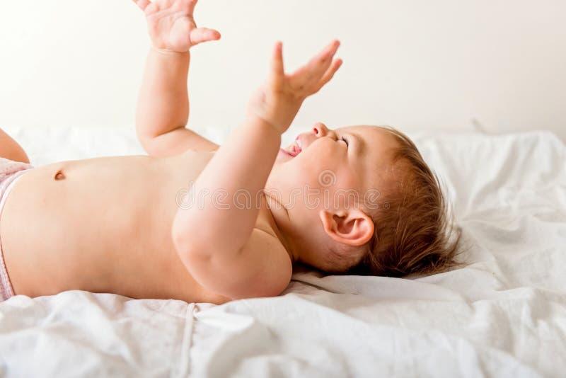 放置在白色卧具和微笑的愉快的小小孩 r E 图库摄影