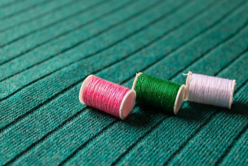 放置在绿色纺织品背景影像的三五颜六色的缝合针线 免版税库存照片