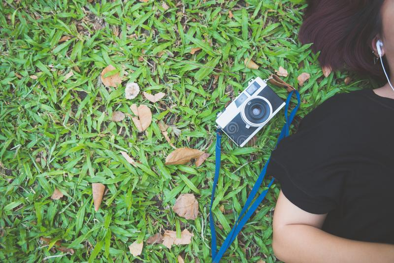 放置在绿草的年轻亚裔妇女听到音乐在公园激动寒冷的 免版税库存照片