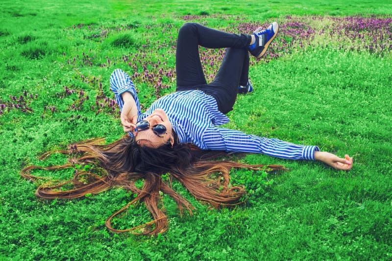 放置在绿草的年轻女人 库存照片