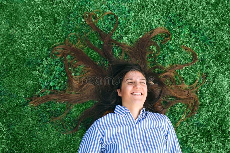 放置在绿草的年轻女人 图库摄影