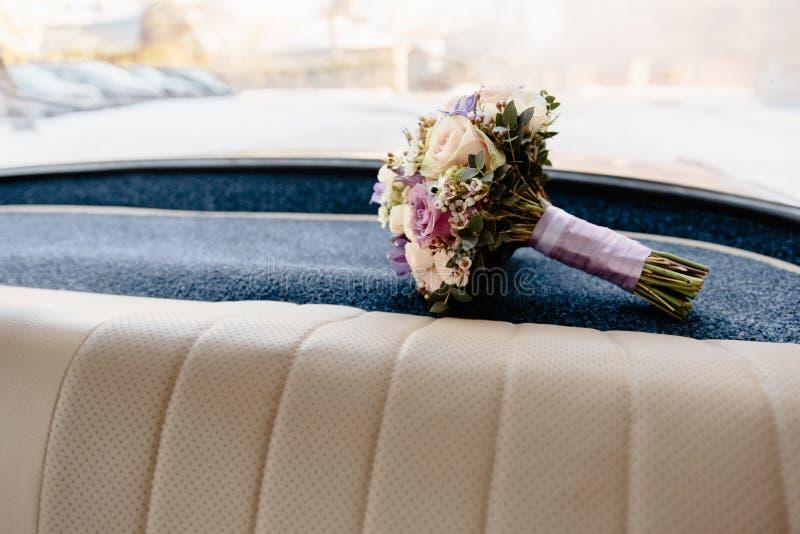 放置在老葡萄酒德国汽车内部的婚姻的花束 图库摄影