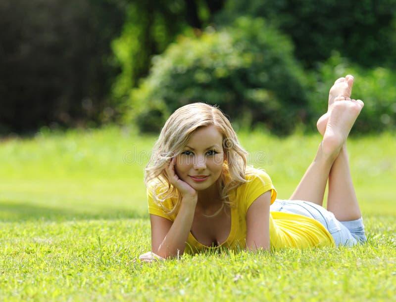 放置在草和微笑的白肤金发的女孩。看照相机。室外。晴天 库存照片