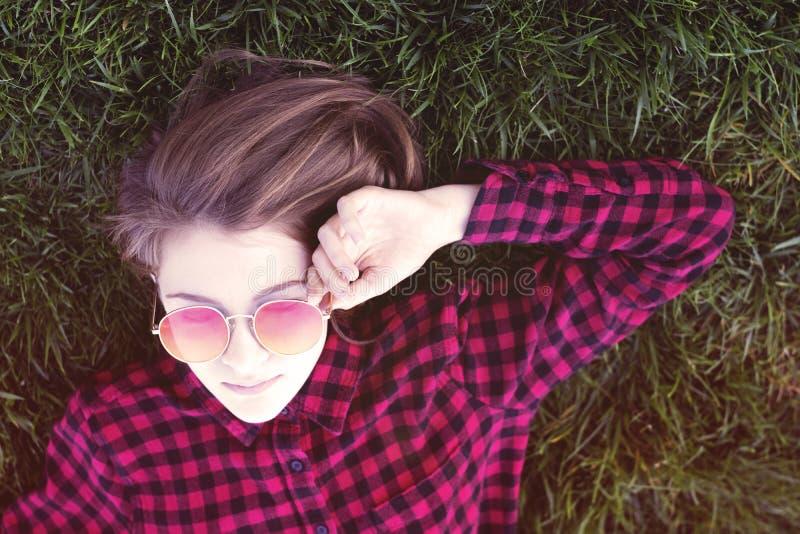 放置在草的十几岁的女孩在太阳镜的公园 免版税库存照片